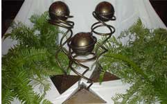 Three New Freedom Awards sit on a white table. Each bronze award is unique and was handcrafted by artist Robert Sadlemire. The award is 30 inches tall with a 12 inch base. Rising from the pyramid-shaped base are two spirals which support a sphere at the top.