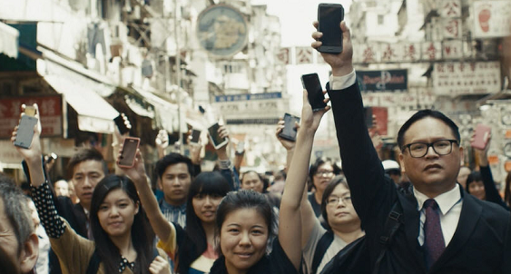 Group of people standing in the street holding up their mobile devices.