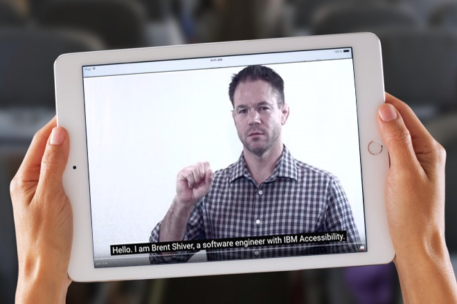 "A person holds an iPad and watches a captioned video of Brent Shiver with captions that say, ""Hello, I am Brent Shiver, a software engineer with IBM Accessibility."""