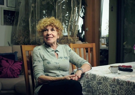 Elderly woman sitting at her dining room table.