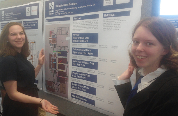 Two female UMass Boston engineering students stand on either side of a board that presents their findings of the Accessible Location-based Services project.