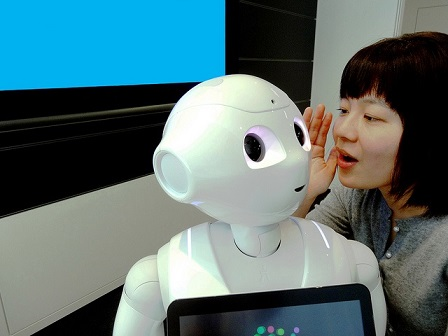 Woman whispering into the ear of Pepper the robot.