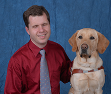 Photo of Tom Babinszki and his guide dog, Baldwin.