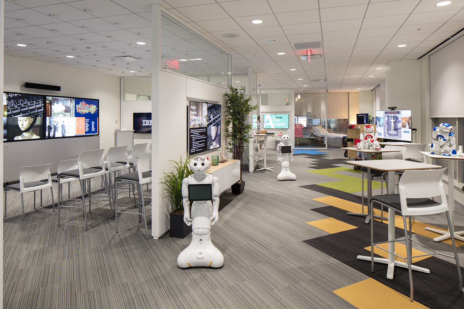 Photo of the IBM Aging-in-Place environment in Austin, Texas. Looking down a long room with four different robots standing and sitting on tables.