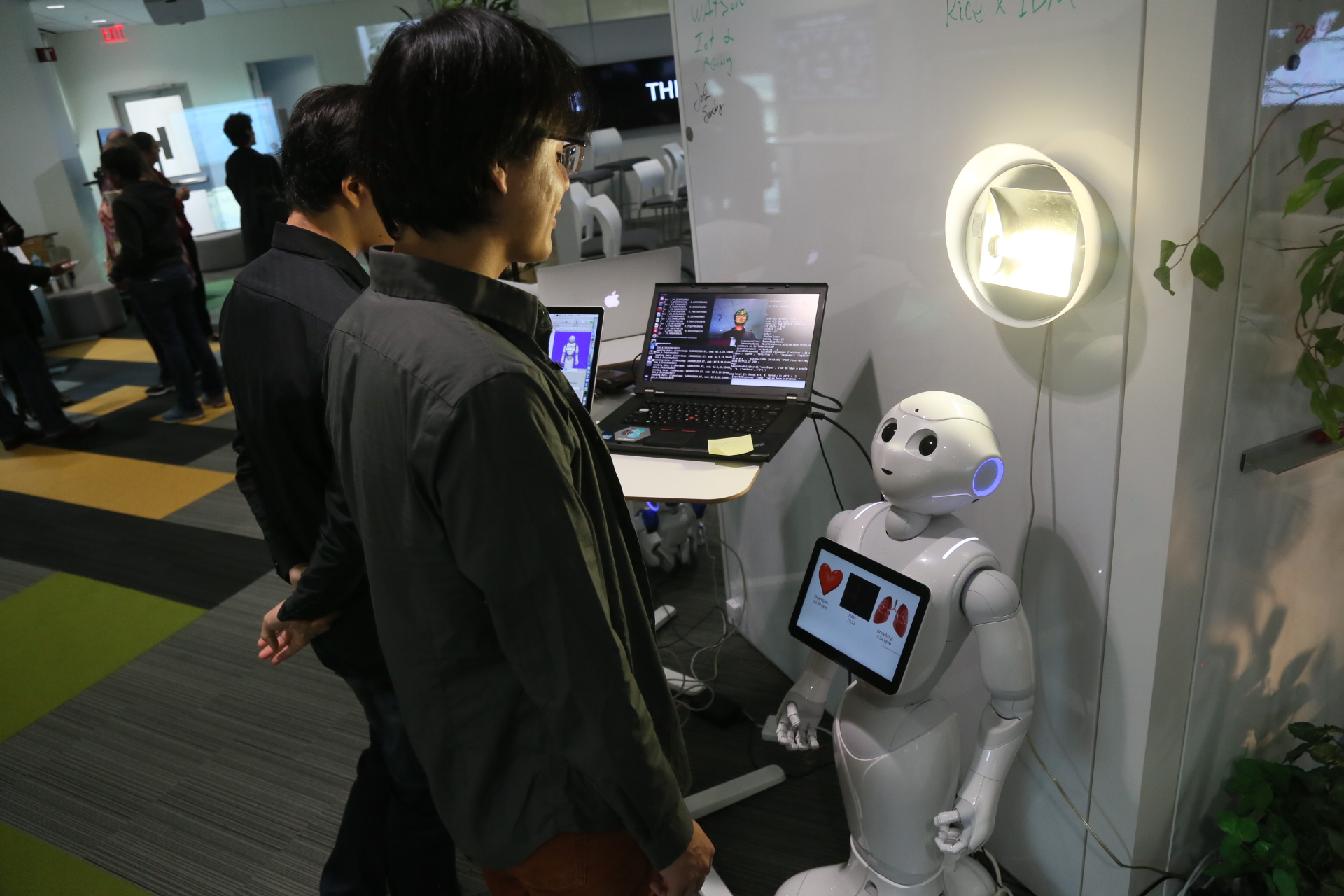A man stands facing a SoftBank Pepper robot. The robot is leveraging its camera to measure the man's vital signs, such as heart rate, and displays it on an iPad mounted to the front of the robot.