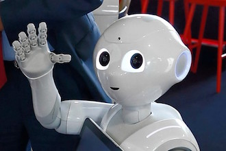 A Softbank Pepper robot looks and waves.