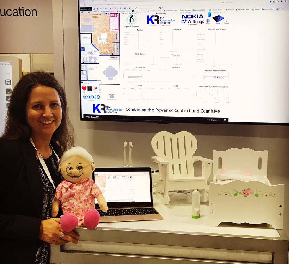 IBM Research Susann Keohane stands holding a grandma doll in front of a demo of grandma's house, which includes props, such as her bed and chair.