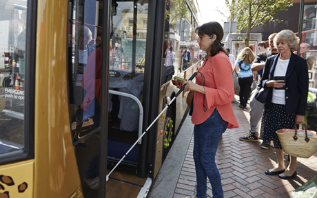 A blind woman boards a bus while other people wait in a line behind her.