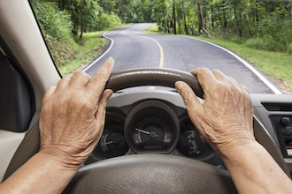 Photo of an elderly person's hands on a steering wheel. View is through windshield at a two-lane road with trees on either side.