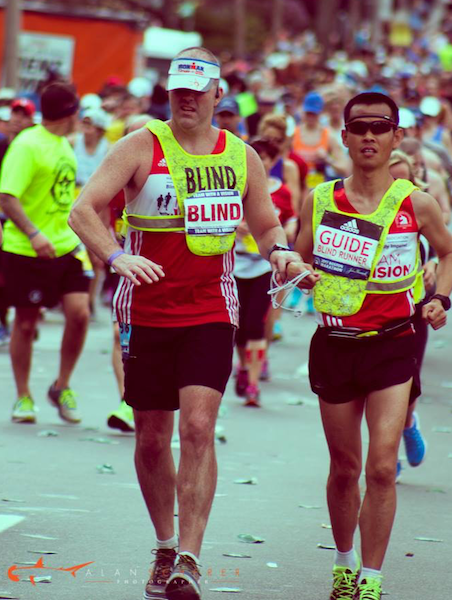 IBM colleagues Erich Manser and David Wei run the Boston Marathon. David is guiding Erich, who is blind, by using a rope tether between them.