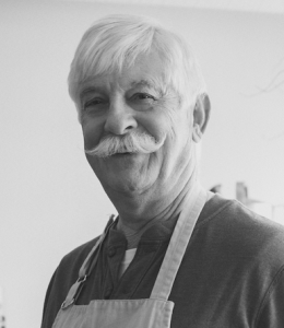Photo of an elderly man with white hair and white mustache, smiling and looking at the camera.