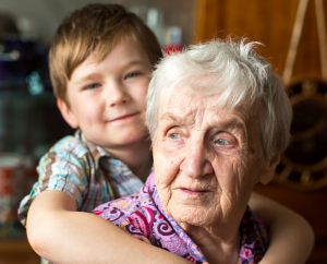 Photo of young boy with arms around an elderly woman.