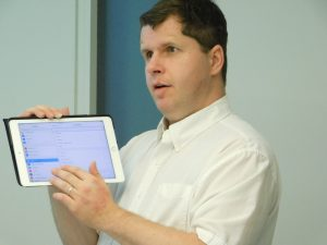 Photo of Tom Babinszki holding an iPad and demonstrating how he uses a screenreader.
