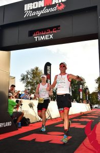 Picture of Erich Manser crossing the finish line at the Maryland Ironman race.
