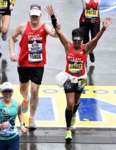 Erich Manser and Bhumika Patel crossing Boston Marathon finish line.