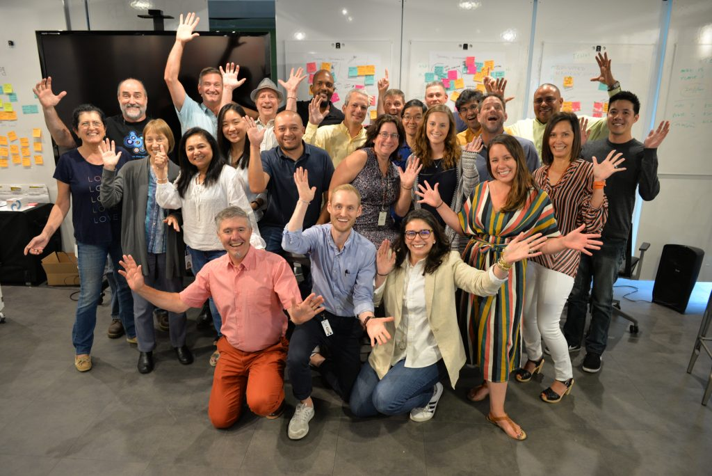 The IBM Accessibility team: a group of smiling people with outstretched arms in front of whiteboards with colorful sitckies.