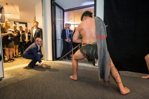 Man receving traditional Maori welcome.