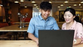 male student at laptop with teacher