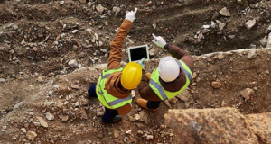Photo of two male workers pointing outward on a construction site
