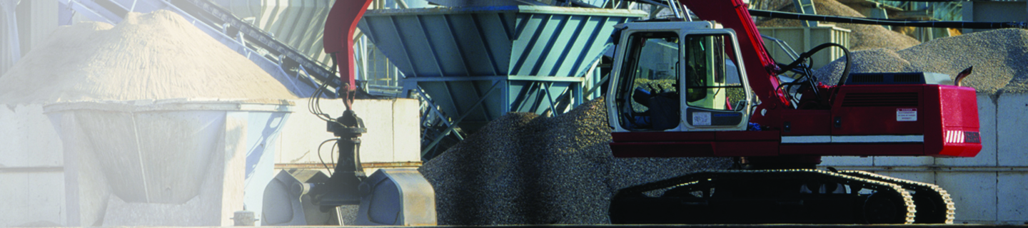 Image shows a cement mill or plant where raw elements are taken through belt conveyor for the production of cement. Cement mill has large silos, chimneys and in front of the mill there is an excavator, heap of gravel and sand.