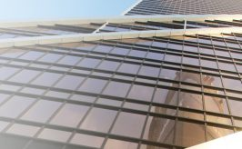Photo of a skyscraper take from the ground up, showing the sun's reflections on the shiny, mirrored finish of the modern building