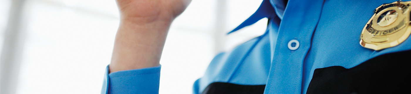 Close-up view of police officer engaged in a conversation using walkie-talkie. Cop wears blue uniform with black above the pockets. There is a window in the background.