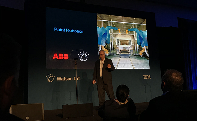 Doug Voda, ABB speaking on stage with image of Paint Robots on slide behind him