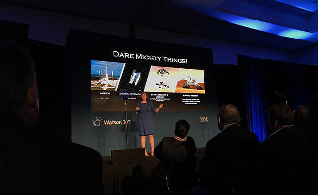 "Tracy Van Houten of NASA on stage in front of slide that says ""DARE MIGHTY THINGS"""