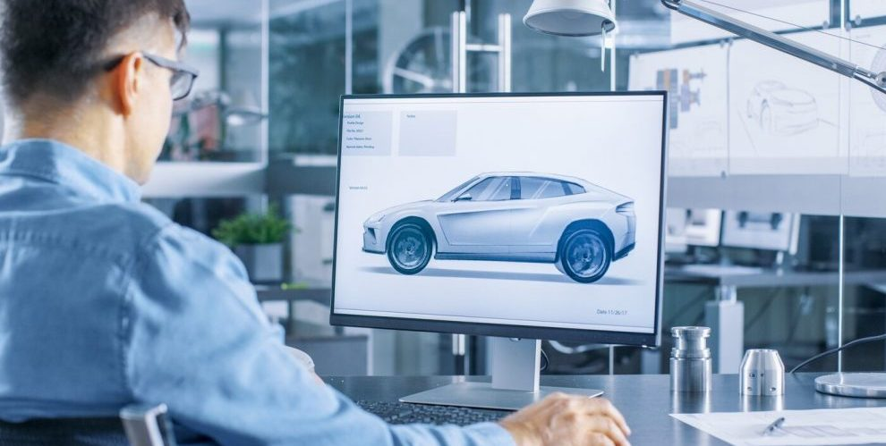 Man in an office looking at digital twin of an car on his computer screen