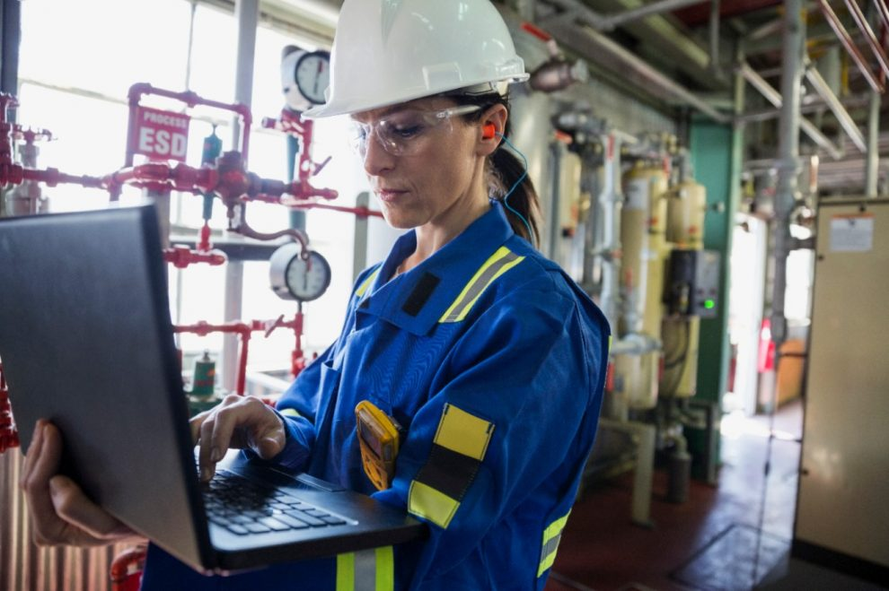 Woman in hard hat checking oil and gas equipment