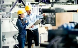 Two people in hard heads looking an manufacturing equipment