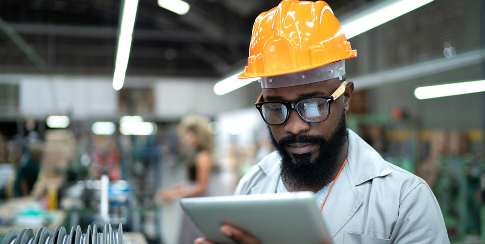 Man with tablet in manufacturing plant