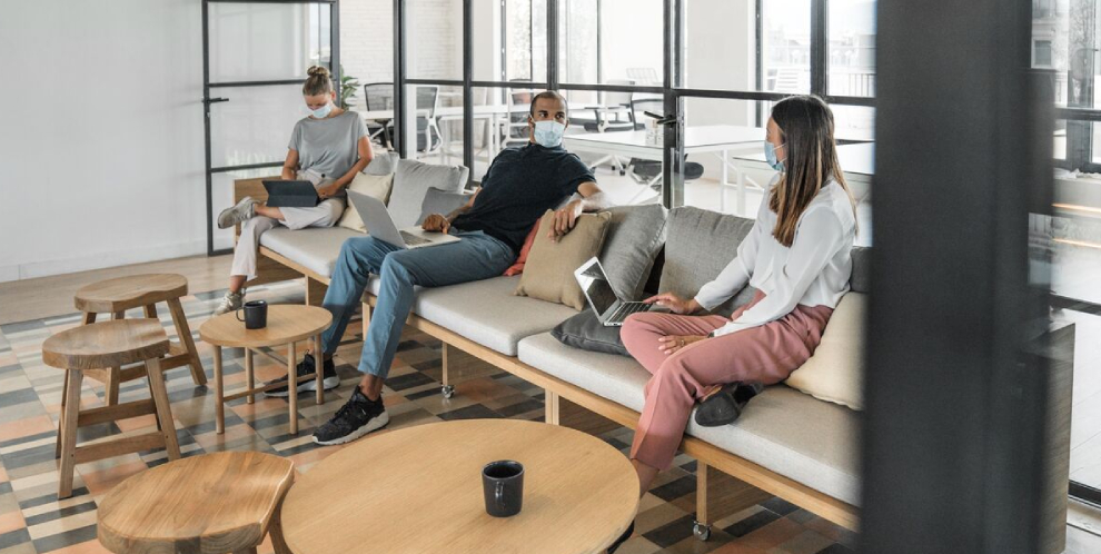 Masked employees in office maintaining distance