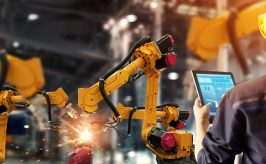 Man with tablet near a factory robotic arm