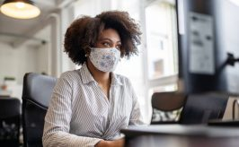Business woman in mask at desk