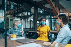 Three people wearing surgical masks having a conversation in an office
