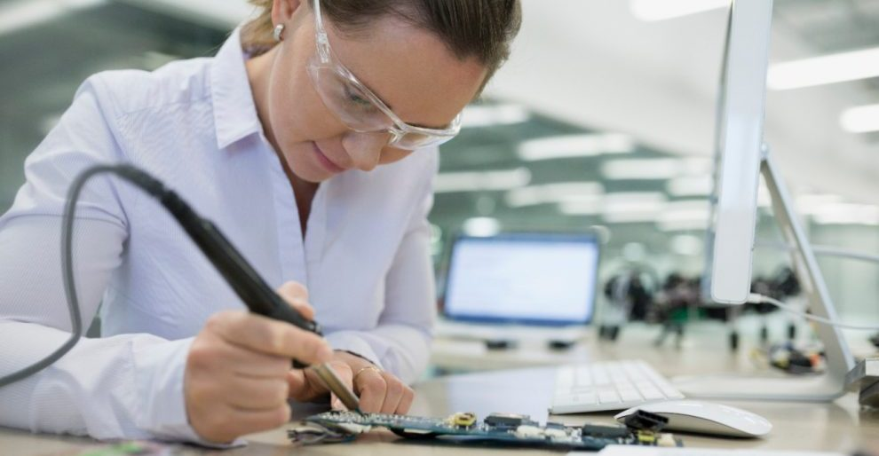 Woman sitting at a desk working on a circuit board with a soldering gun.