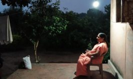 Woman in India sitting under a porch light outside at night