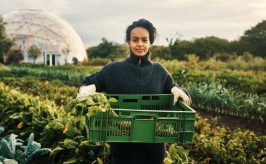 Woman in greenhouse holding a box of fresh produce