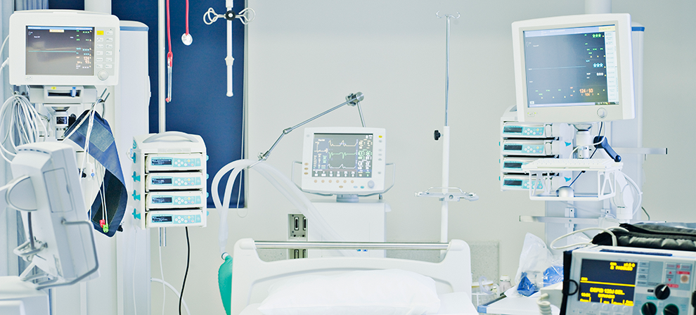 Medical monitors and devices around an empty hospital bed