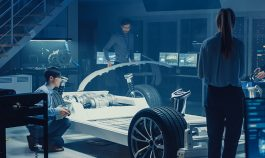 Four people designing a vehicle in a room using multiple gadgets and physical automobile components