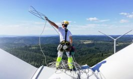 technician standing on roof (hub) of wind turbine and pulling rope up. Sun is behind wind turbine.