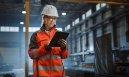 Professional Heavy Industry Engineer Worker Wearing Safety Uniform and Hard Hat, Using Tablet Computer