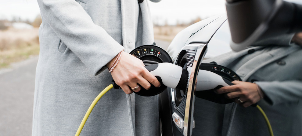 A person wearing an overcoat plugging in the charging cable into an electric vehicle