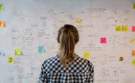 A woman standing in front of a chart paper filled with diagrams and colorful post it notes