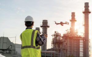 Construction worker piloting drone at industrial site to use for inspecting equipment