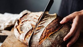 person cutting bread with knife
