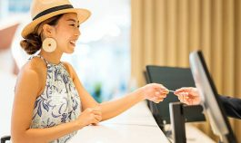 woman giving card to hotel front desk