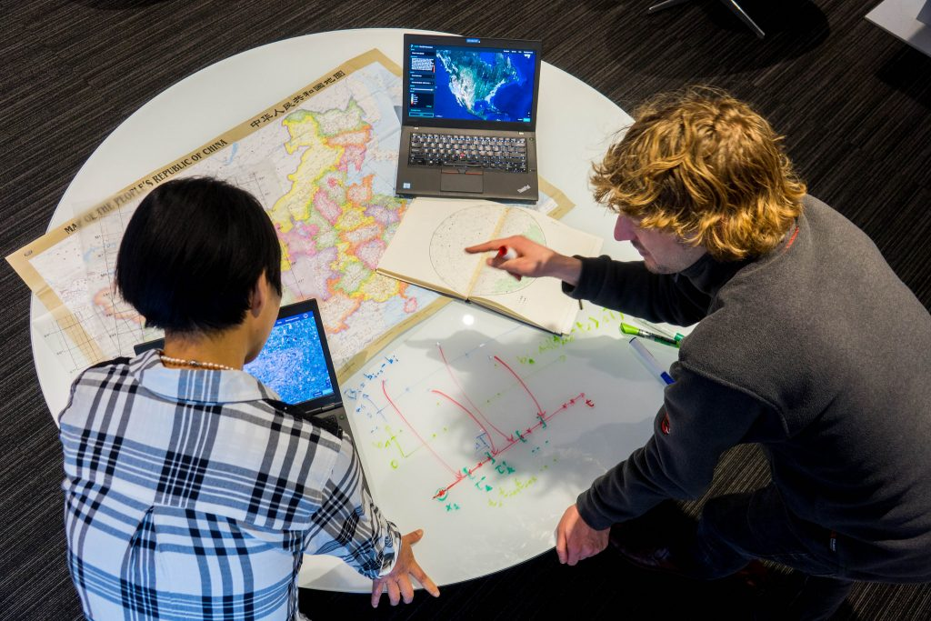 IBM scientists, Xiaoyan Shao (left) and Conrad Albrecht, interact with the IBM PAIRS Geoscope service.