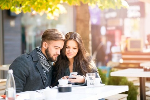 man and woman using their phone